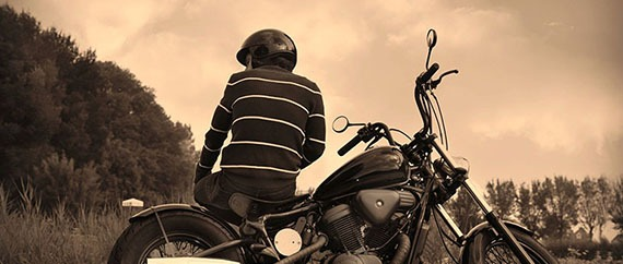 Person with helmet sitting on his custom motorcycle