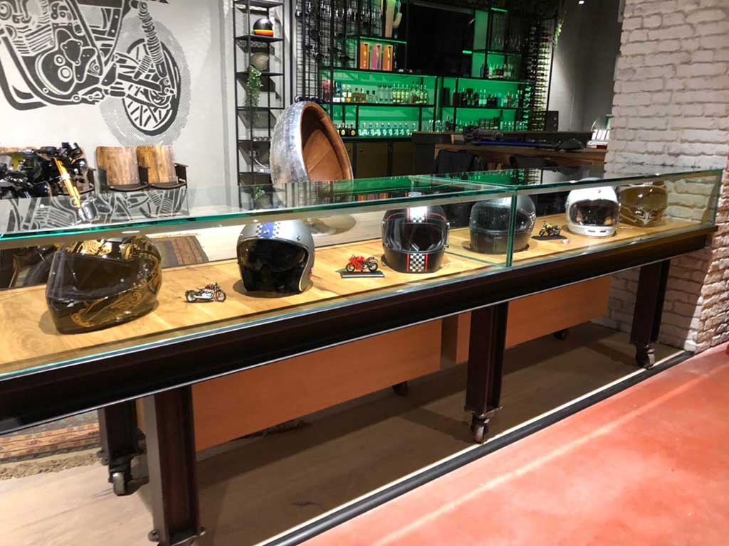 Showcase of helmets and in the background the bar for Lord Drake Kustoms' cafe racer workshop in Madrid